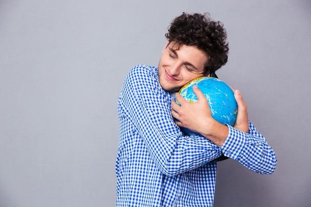 Молодой человек обнимает земной шар
