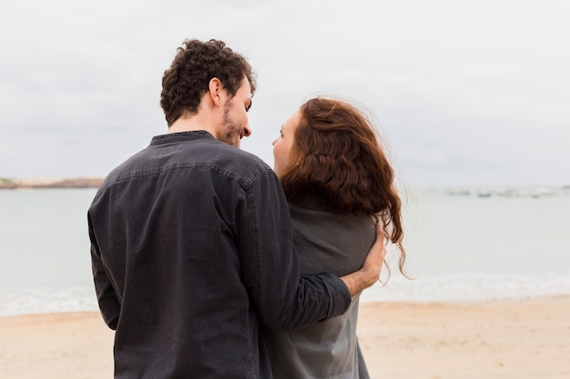 Young man hugging woman in blanket on sea shore