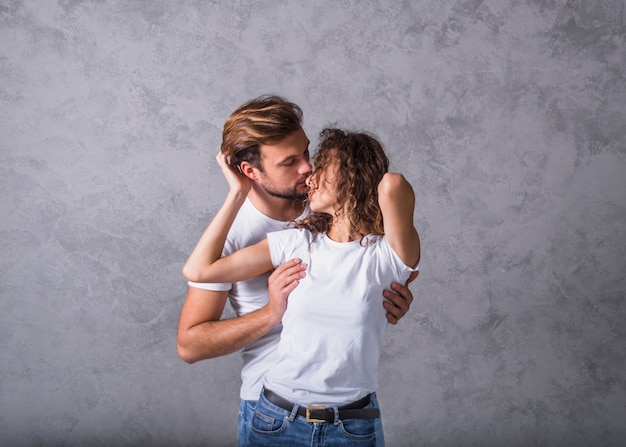 Young man hugging woman from behind