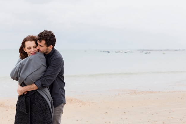 Young man hugging woman in grey blanket on sea shore