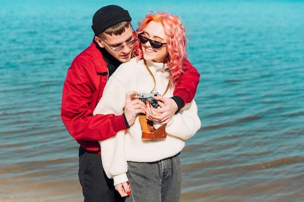 Young man hugging woman and setting photo camera