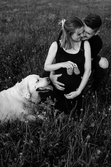 Young man hugs his pregnant wife, who is holding baby shoes in her hands, their smartest bitch is lying next to her. black and white photo. waiting for child. addition to family. funny moments.