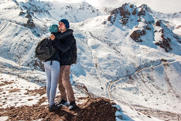 A young man hugs his wife on a background of snowy mountains. holidays in the mountains.