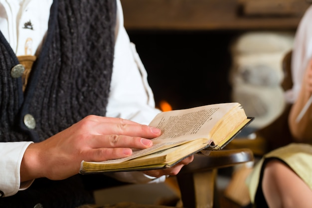 Young man in a hunter's cabin reading the bible