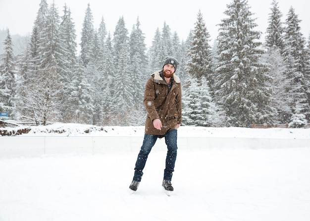 Young man ice skating outdoors with snow