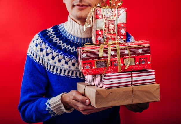 Young man in icelandic sweater holding a heap of gift boxes on red background christmas or new year