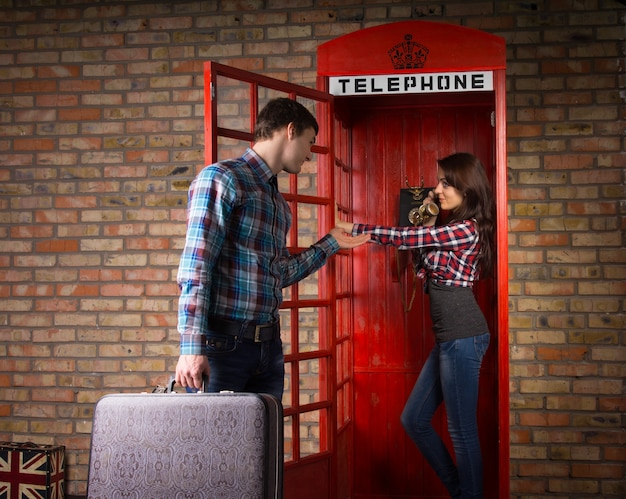 Young man imploring his wife to get off the phone as he stands outside the telephone booth with his suitcase in his hand