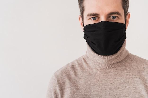 Молодой человек в черной защитной маске. средства индивидуальной защиты от короновируса. домашняя маска для доступа в общественные места