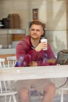 カフェで若い男と窓際に座ってコーヒーを飲む