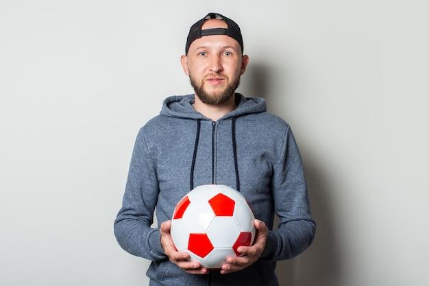 Молодой человек в кепке и толстовке с капюшоном держит футбольный мяч у светлой стены.