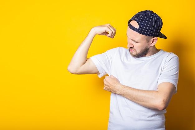 모자와 티셔츠에 젊은 남자가 노란색 배경에 그의 겨드랑이를 막습니다.