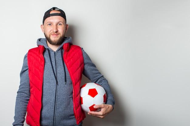 Молодой человек в кепке, толстовке и жилете держит в руке мяч у светлой стены