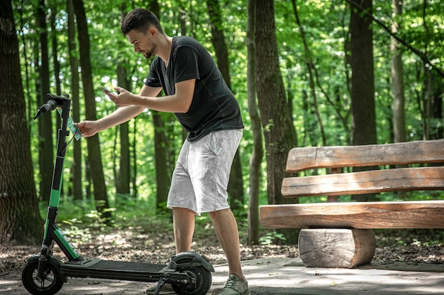 電動スクーターで都市公園の若い男。
