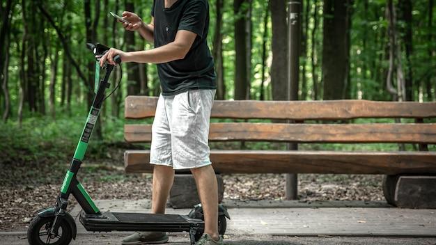 Молодой человек в городском парке с электросамокатом.