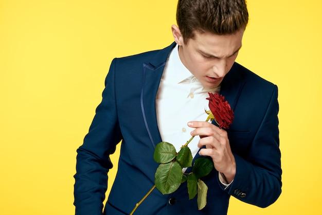 Молодой человек в классическом костюме с красной розой в руке на желтом фоне. модель с обрезанным видом.