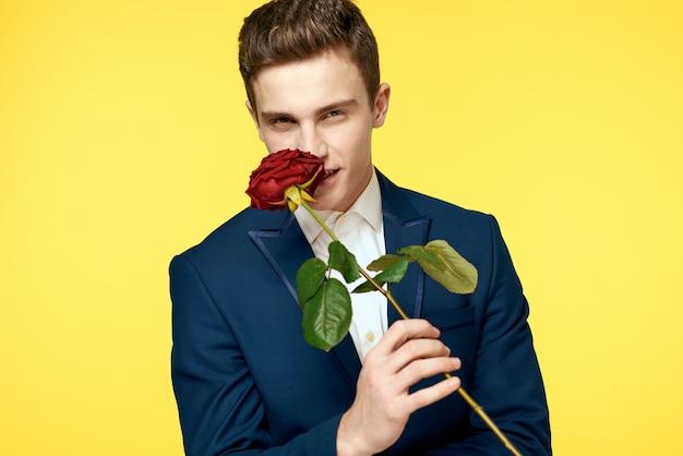 彼の手に赤いバラと古典的なスーツを着た若い男