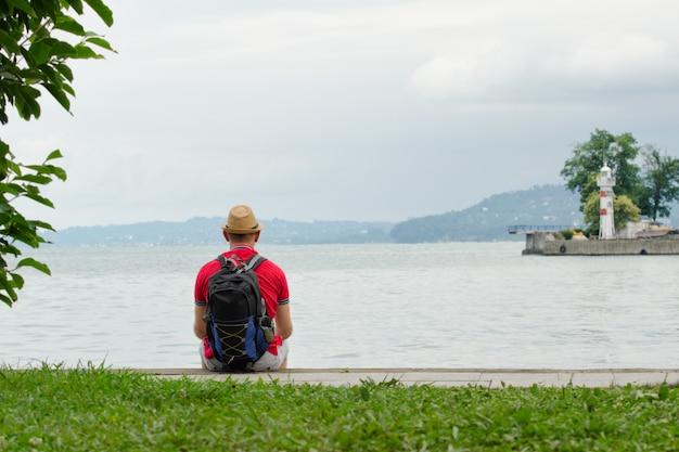 모자와 배낭 젊은 남자는 바다의 배경에 부두에 앉아있다
