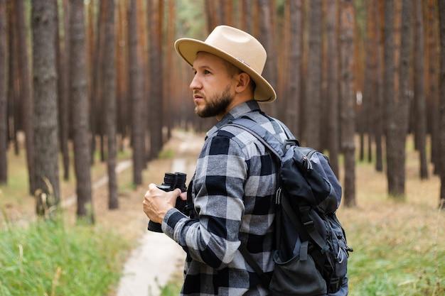 배낭과 소나무 숲에서 쌍안경 모자에있는 젊은이. 산이나 숲에서 하이킹.