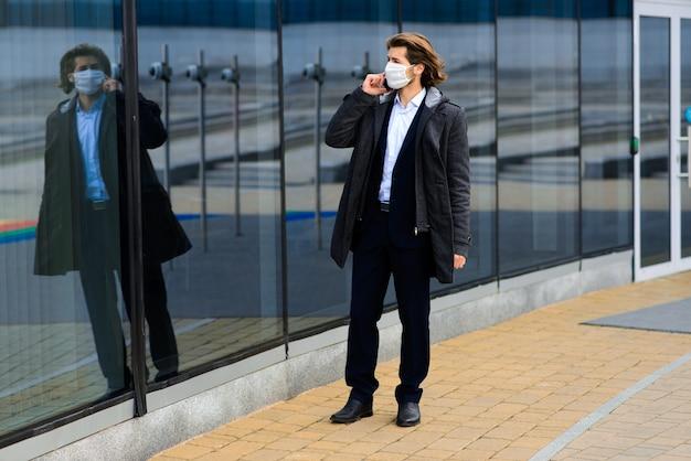Молодой человек в медицинской маске снаружи, без денег, кризиса, бедности, лишений. коронавирус изоляция.