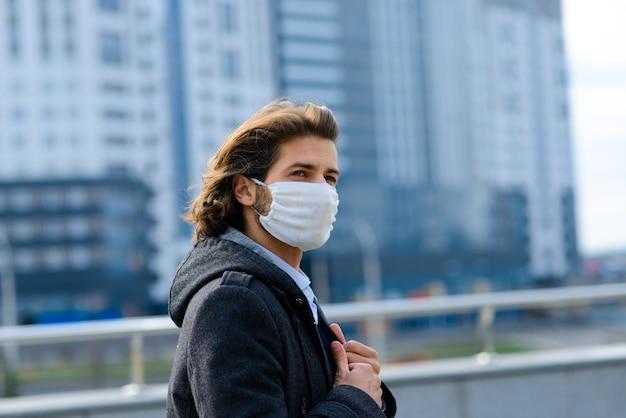 外の医療マスクの若い男、お金、危機、貧困、苦難。コロナウイルス隔離。