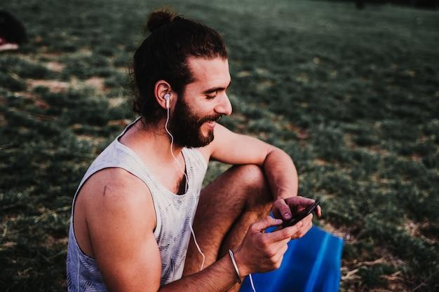 Молодой человек в парке, слушая музыку на мобильном телефоне