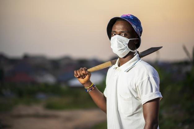 シャベルを保持している保護フェイスマスクの若い男
