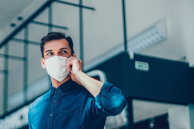 Молодой человек в защитной маске выбирает контакт в своем смартфоне. пандемия в городе