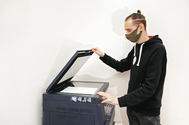 보호 마스크의 젊은 남자가 사무실의 복사기에 문서 사본을 만듭니다.