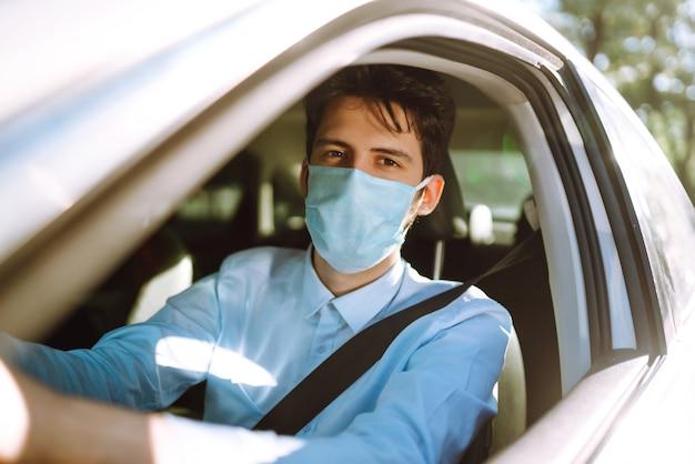 車に座っている保護マスクの若い男