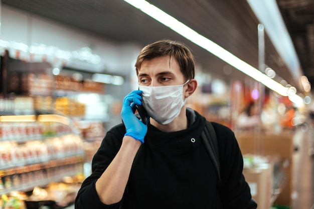 彼のスマートフォンで話している保護マスクの若い男