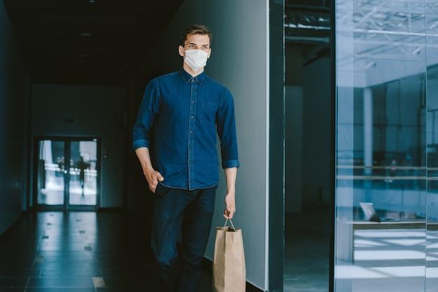 Молодой человек в защитной маске гуляет по улице города. коронавирус в городе