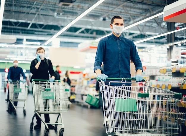 ショッピングカートと保護マスクの若い男
