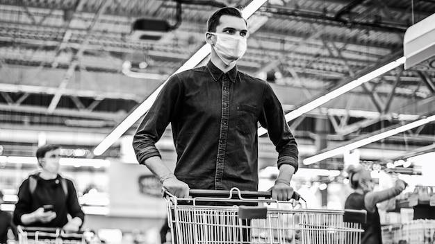 Молодой человек в защитной маске с тележкой для покупок