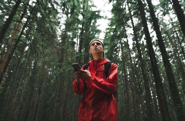 赤いジャケットを着た若い男がハイキング中に森の中に立って電話を使用します