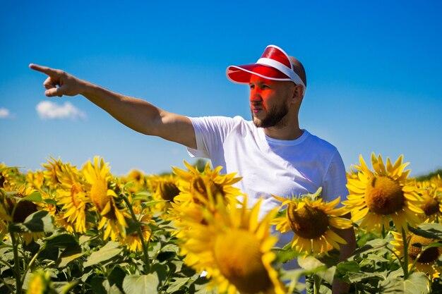 Молодой человек в красной тени на голове указывает рукой на солнце на подсолнечном поле в ясный день.