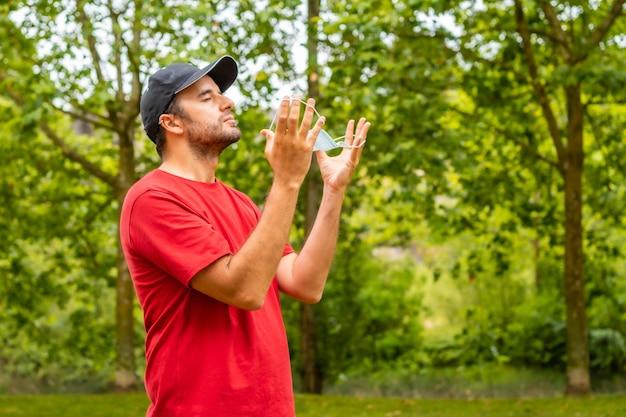 나무 배경으로 수술용 마스크를 제거하는 빨간 티셔츠를 입은 청년