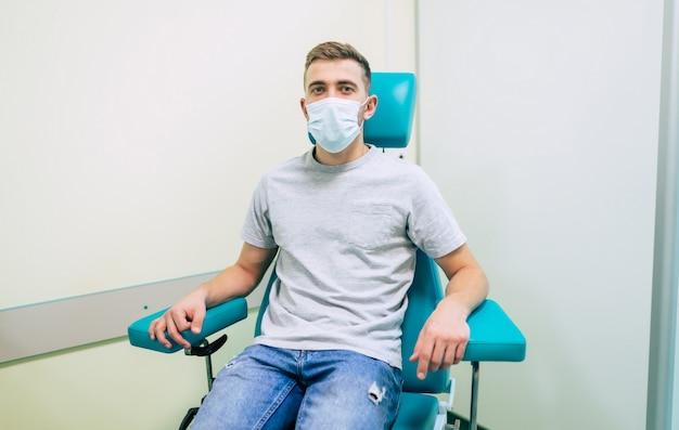 Молодой человек в медицинской маске сидит на больничном кресле и смотрит в камеру