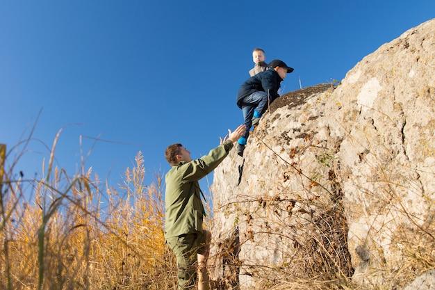스카우트 제복을 입은 청년 두 명의 어린 소년이 아래에서 손으로 그들을 지원하는 광야의 바위 절벽을 오르는 것을 돕는