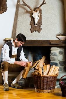 Молодой человек в традиционной горной хижине с камином