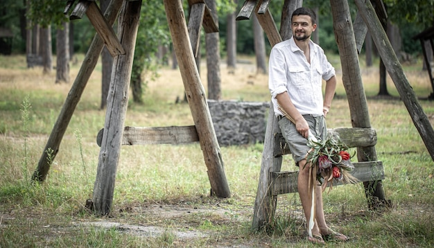 Молодой человек в белой рубашке держит букет экзотических цветов, концепция свиданий.