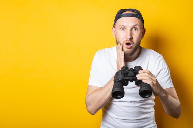 Молодой человек в белой футболке и бейсболке удивлен и шокирован держит бинокль.