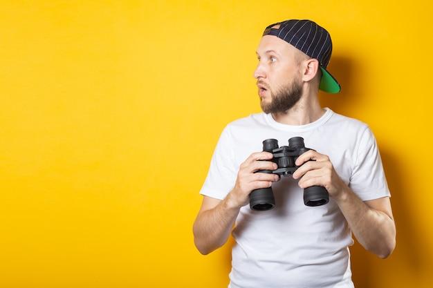 Молодой человек в белой футболке и бейсболке с удивлением смотрит в сторону держит бинокль.