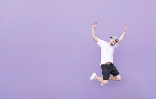 Молодой человек в белой футболке и черных шортах в прыжке на фиолетовом фоне