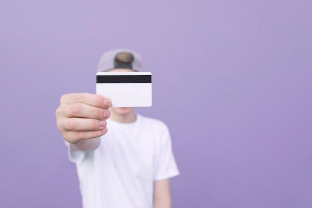 彼の手が紫色のパステル背景に立っている銀行カードと白いtシャツを着た若い男