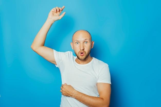 Молодой человек в белой футболке с мокрыми подмышками от пота на синем фоне