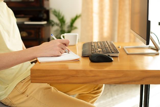 のtシャツを着た若い男が自宅のコンピューターで動作します。オンラインチャット。コロナウイルスの隔離中の隔離に関するインターネットを介したリモート作業。フリーランサー