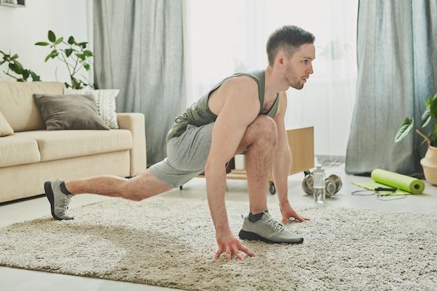 Молодой человек в активной одежде растягивает ногу, делая упражнения и потеет в домашней обстановке, проводя дни в своей квартире