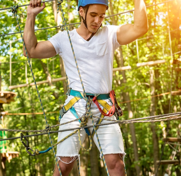 Молодой человек в веревочном парке приключений. альпинистское снаряжение. использование ремня безопасности и защитных шлемов.
