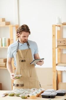 タブレットpcと配達用の新鮮な野菜の梱包箱を使用してエプロンの若い男