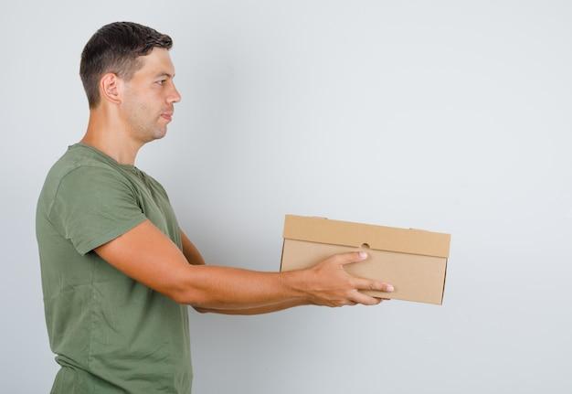 Молодой человек в зеленой футболке армии доставляя картонную коробку.
